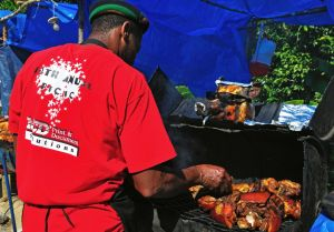 13. Back up to town from the Kindah Tree, the vendors are ready to sell some jerk pork.