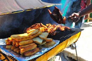5. Traditional Jamaican food vendors prepare their grills early. Foods include festival, and jerk pork or chicken..